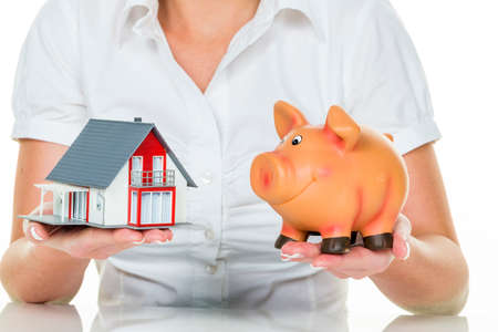 woman with house and piggy bank