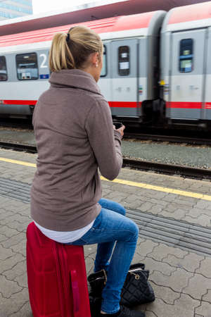 woman is waiting for train and texting Standard-Bild