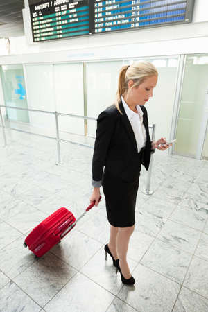 woman with suitcase and mobile phone at the airport Standard-Bild