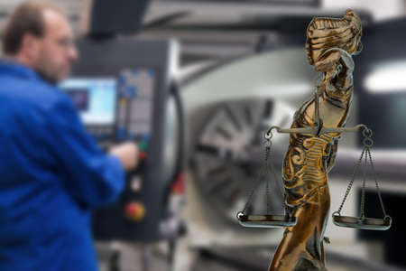 Worker with justitia statue. Symbol for emplyment law Stock Photo