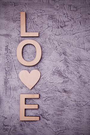 8bba0357e26186 Vertical wooden love letters rustic gray background. toned. Stock Photo