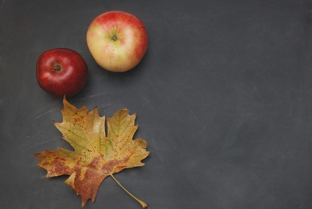 Black Chalkboard Background With Red Apple And Maple Orange Leaves Autumn Concept Stock Photo