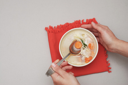 Hand holding a bowl with soup with