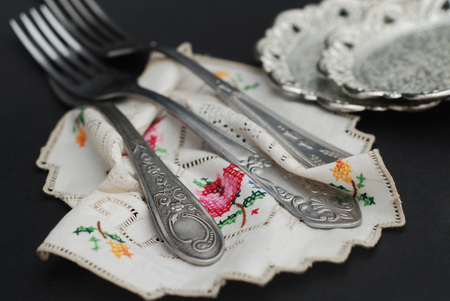 Rustic silver spoons collection on embroidery napkin Stock Photo