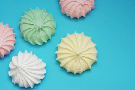 Colorful Meringues on Blue. Many sweet zephyrs
