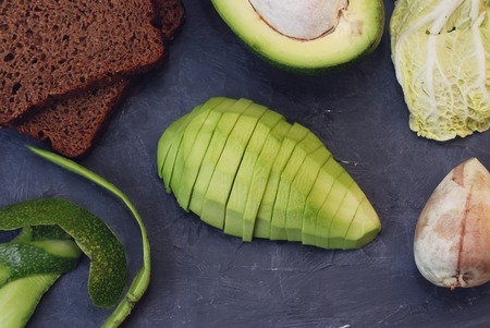 Sliced ripe avocados on Dark cutting board. Vegan and Health Food Concept Stock fotó