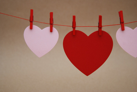Red and Pink Paper Hearts on rope, Isolated on Brown Background. Love and Valentines Day. Stock Photo