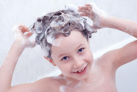 Niña linda que tiene un baño en agua de espuma. Niño lavándose el pelo largo. De cerca. Enfoque selectivo en la cara de los niños.