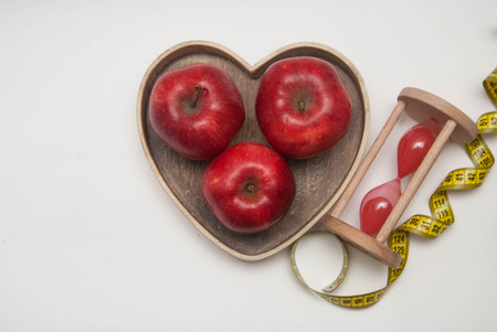 Healthy Food Concept. Diet and Fitness. Glass Clock and Red Apple in Heart Shape Wooden Box. Measuring Tape . Stock Photo