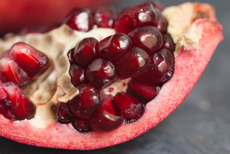 Pomegranate Slice Fruit. Close up Granate Seeds in slice. Macro image. vitamine and Healthy concept. Stock Photo