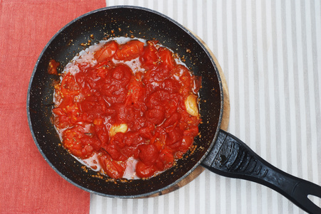 Tomatoe Sauce in Black Pant Top view. Food Preparing with Orange Napkin. Top view. Stock Photo