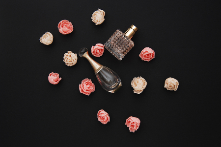 Bottle Perfume and Fake Roses on dark Black Background with copy Space Top view