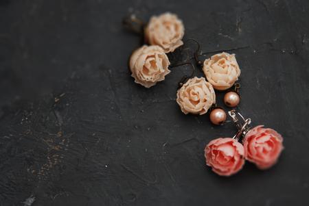 Mix of Fake Plastic Mini Rosess Pink and Peach color Earings Black Round Plate Copy space. Stock Photo