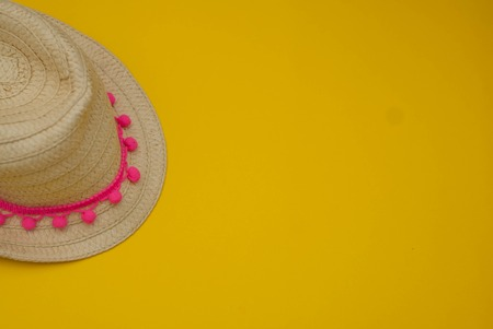 Yellow Straw Hat over Summer Yellow Background Holliday