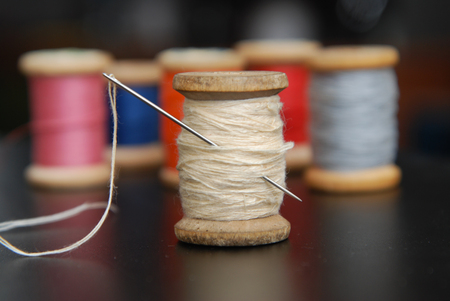Close up Rolls of Vintage Colorful Threads. Clothes Repair, Black Dark Background. Sewing work Foto de archivo