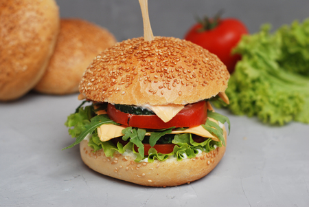 Fast food. Vegetarian Homemade Burger Cheese, Cucumber, Tomato and Lettuce, Salad. Tasty Sandwich for lunch Fresh Vegetables. Gray Textured Table Stock Photo
