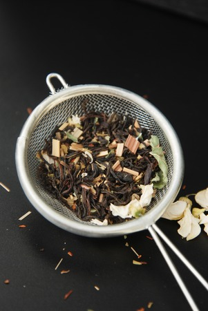 Herbal tea Healthy Drink in bowl and sieve over Black Background