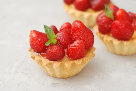 Sweet Dessert Tartlets with Strawberries and Cream Isoalted over Gray Textured Background.