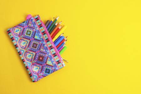 Schulsachen der Buntstifte im gelben Hintergrund des rosa Gehäuses. Zurück zur Schule. Standard-Bild