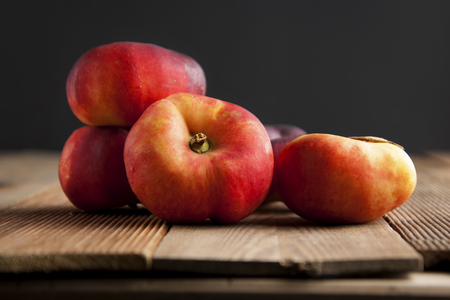 Peaches and Nectarines fruits. Concept for healthy nutrition. Dark black background and wooden table.