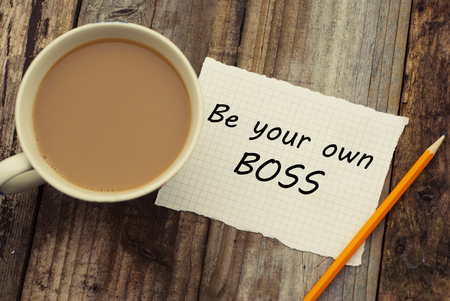 Be Your Own Boss motivational inscription on white paper, with cup of coffee. Top view.