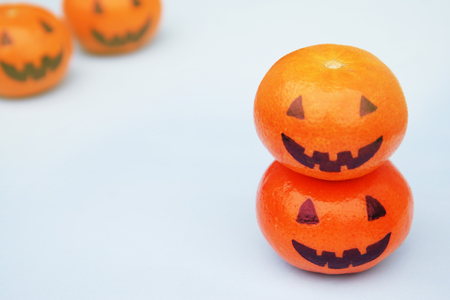 Funny orange mandarins or tangerines pumpkin painted in the form of icons of Halloween