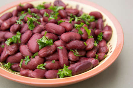 Cooked red beans plate on pink background, isolated.