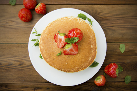 Delicious homemade american pancakes with fresh strawberry and honey.