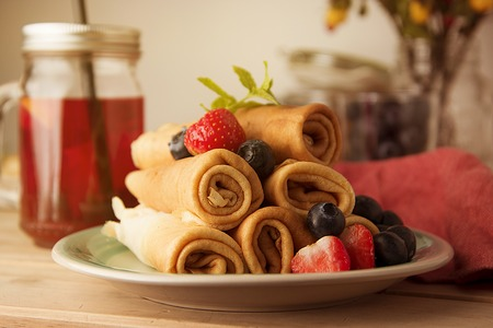 Rolled up crepes, pancakes on a plate with blueberries and strawberries.