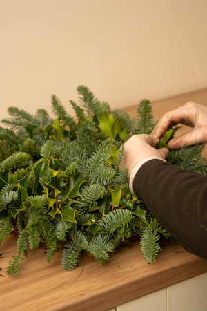 Florist at work: woman making natural Christmas wreath, christmas decorations
