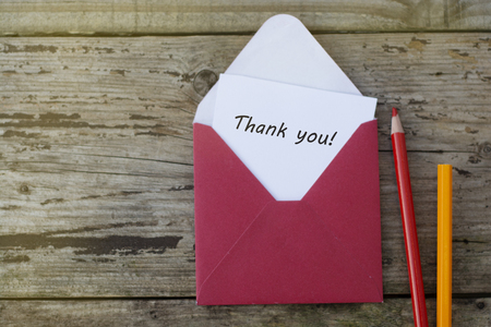 Thank you inscription - red envelope with blank card on wooden background with copy space, and red pencils.