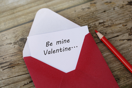 Be mine Valentine inscription - red envelope with blank card on wooden background with copy space, and red pencils.