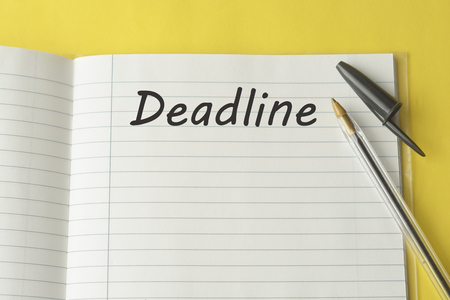 Deadline word writen on white blank paper, notebook and pen on colorful yellow background