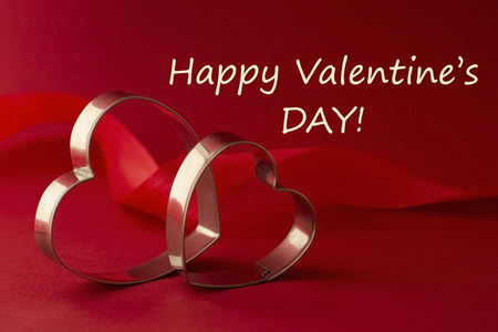 Happy Valentine's Day inscription. Greeting card. Two red heart shaped cookie cutters on beautiful red background.