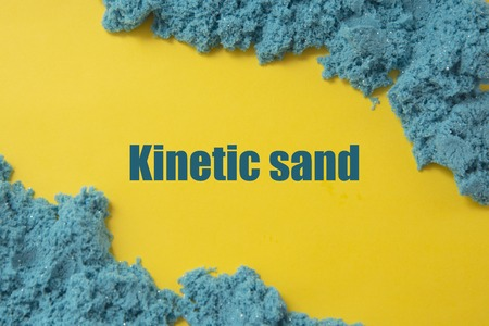 Abstract blue textured kinetic sand over yellow background. Kinetic sand word. Stok Fotoğraf