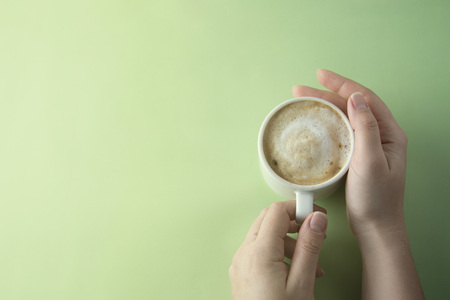 Female hands holding a cup of coffee with foam over green