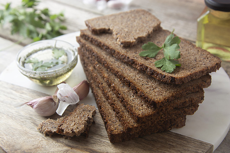 Sliced wholegrain bread wit seeds, greens, oil and garlic on cutting board. Top view.