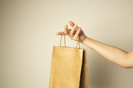 Primer plano de una mano femenina que sostiene el paquete de papel artesanal., Maqueta de diseño. Concepto de cero easte. Sin plástico. Protege el planeta.