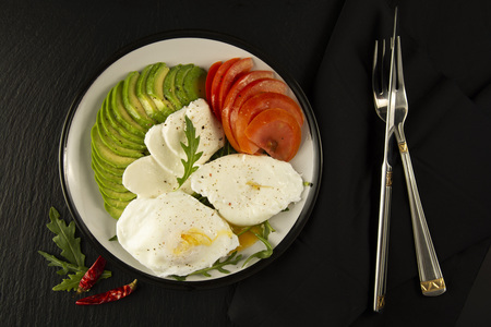 Avocado poached eggs. Healthy breakfast food and tomato on black background. Close up food.