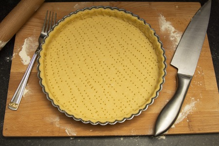 Raw, uncooked tart pie preparation, dough. Cooking apple, fruit pie. Cookign process Kitchen table