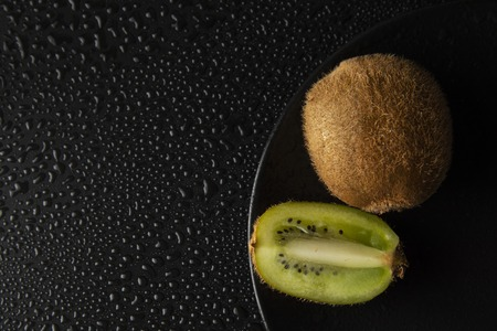 Kiwi fruit isolated on black background, fresh kiwi fruit. Summer vitamine fruit. Healthy food or dessert. Water drops.
