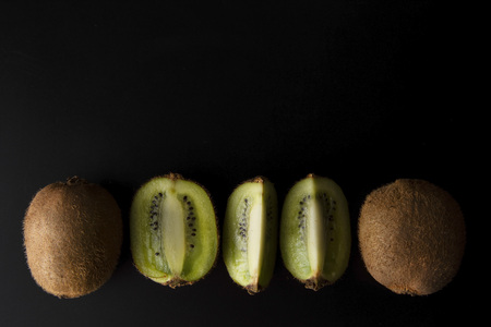 Kiwi fruit isolated on black background, fresh kiwi fruit. Minimalistic fruit background. Healthy food or dessert. Diet, lose weigh.