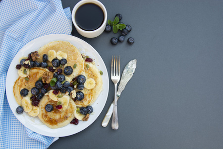 Pancakes on plate with blueberries, mint and honey for breakfast - homemade healthy vegetarian food
