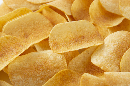 backgrBackground golden potato chips texture. Crispy unhealthy snackound corrugated golden chips with texture Stock Photo