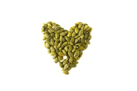 Pumpkin seeds heart shape, on a white background, isolated. Healthy vegetarian snack. Love vegetarian food. Loose weigh or fitness super foods. 写真素材