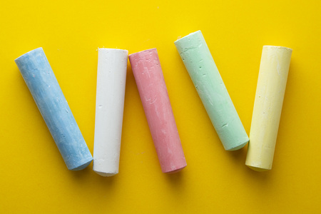 Abstract colorful chalks over yellow background. Education template. Creative childhod, business concept. Top view, copy space.