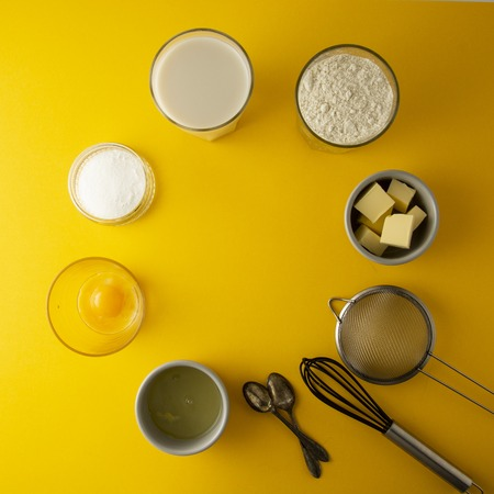 Ingredients for baking pastry or dessert. Butter, flour, eggs, milk, sugar. Yellow background, flat lay. Dessert recipe cooking process