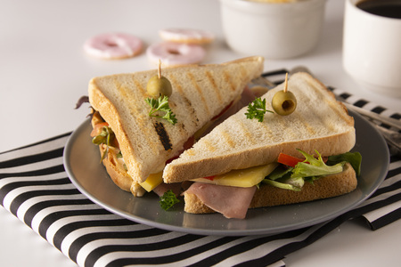 Stylish sandwich. Toasted double panini with ham, cheese fresh vegetables. Snack at work or lunch. Light background. Healthy food.