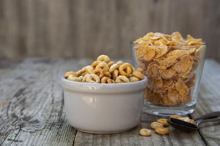 Bol avec des anneaux de maïs et des flocons, petit-déjeuner aux céréales. fond texturé rustique. Alimentation saine pour les enfants. Banque d'images