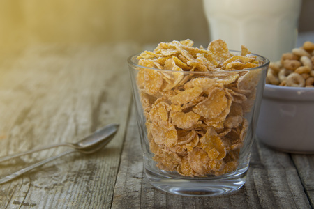 Recipiente con copos de maíz sobre fondo de madera gris